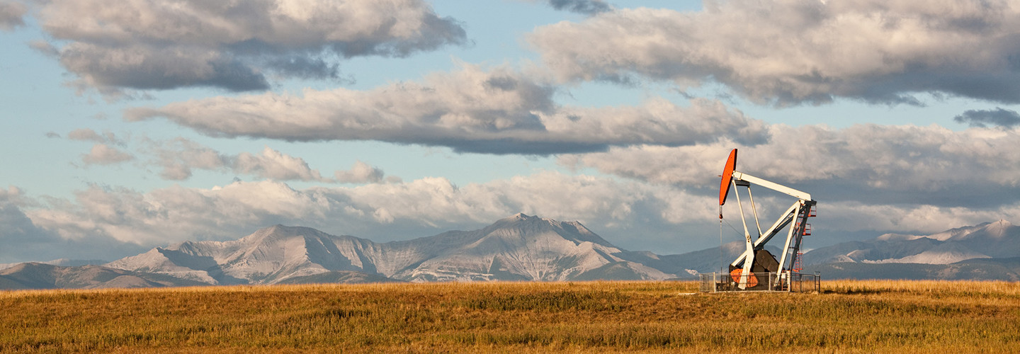 Remote oil well in Alberta, Canada, with mountains in the background