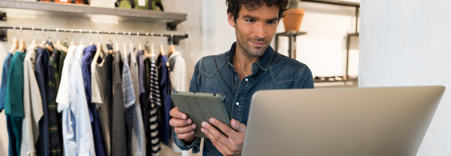 Male retail worker looking at data analytics on a monitor in a retail store