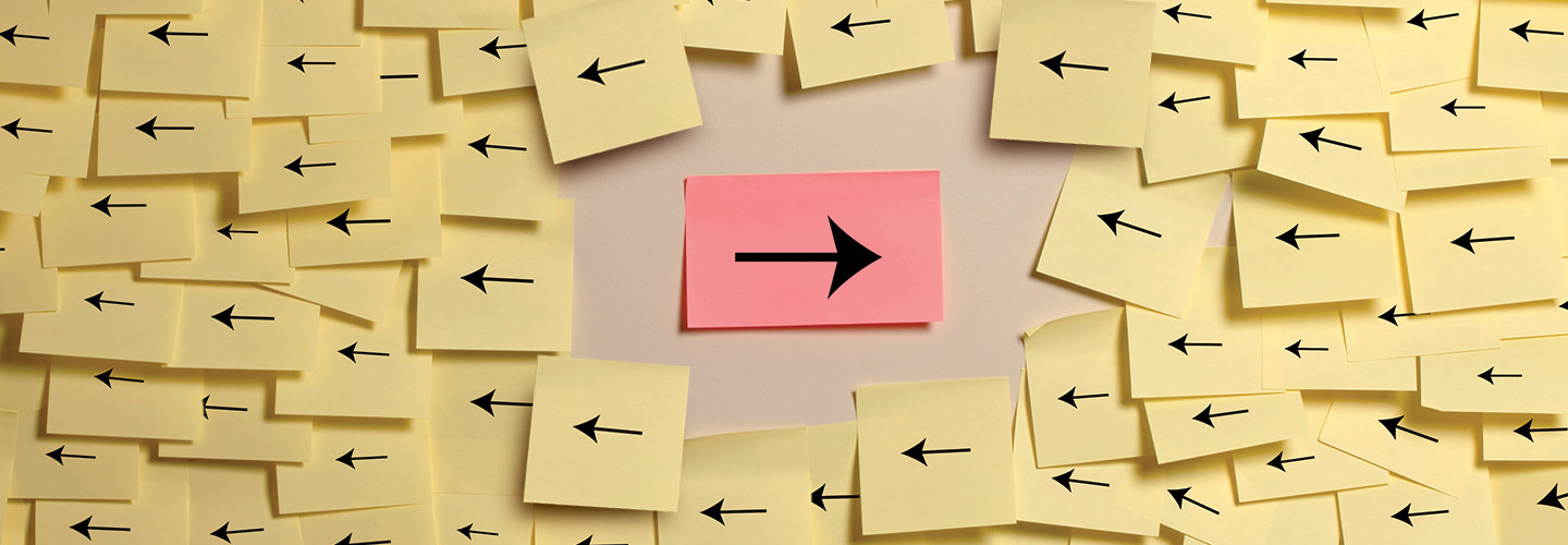 A right-facing arrow on a red post-it note amid a sea fo left-facing arrows on yellow post-it notes