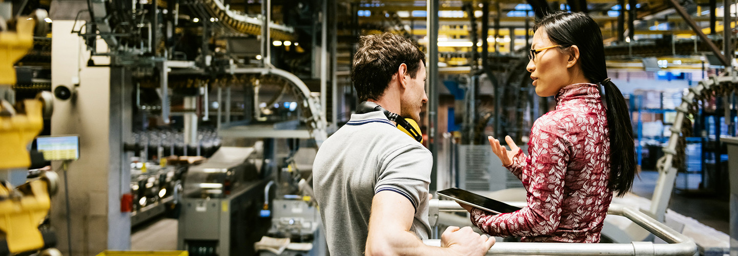 Male and female engineer using technology in a manufacturing plant