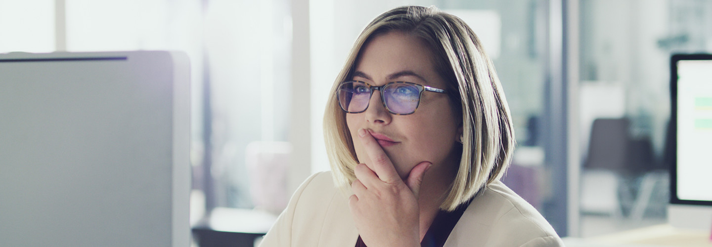 Woman CIO with glasses and dirty blonde hair sitting at her computer and thinking