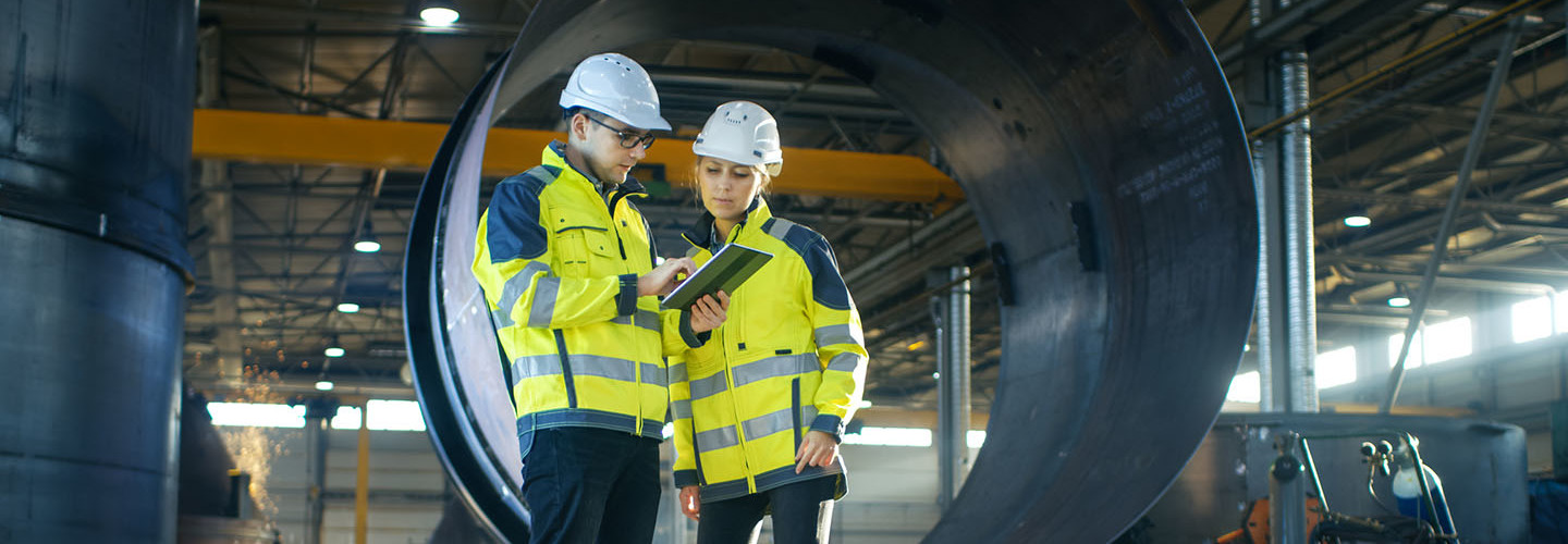 Industrial Engineers in Hard Hats Discuss New Project while Using Tablet Computer