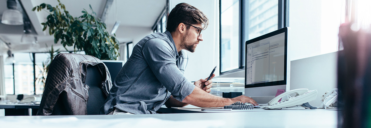 Man at computer in bright office