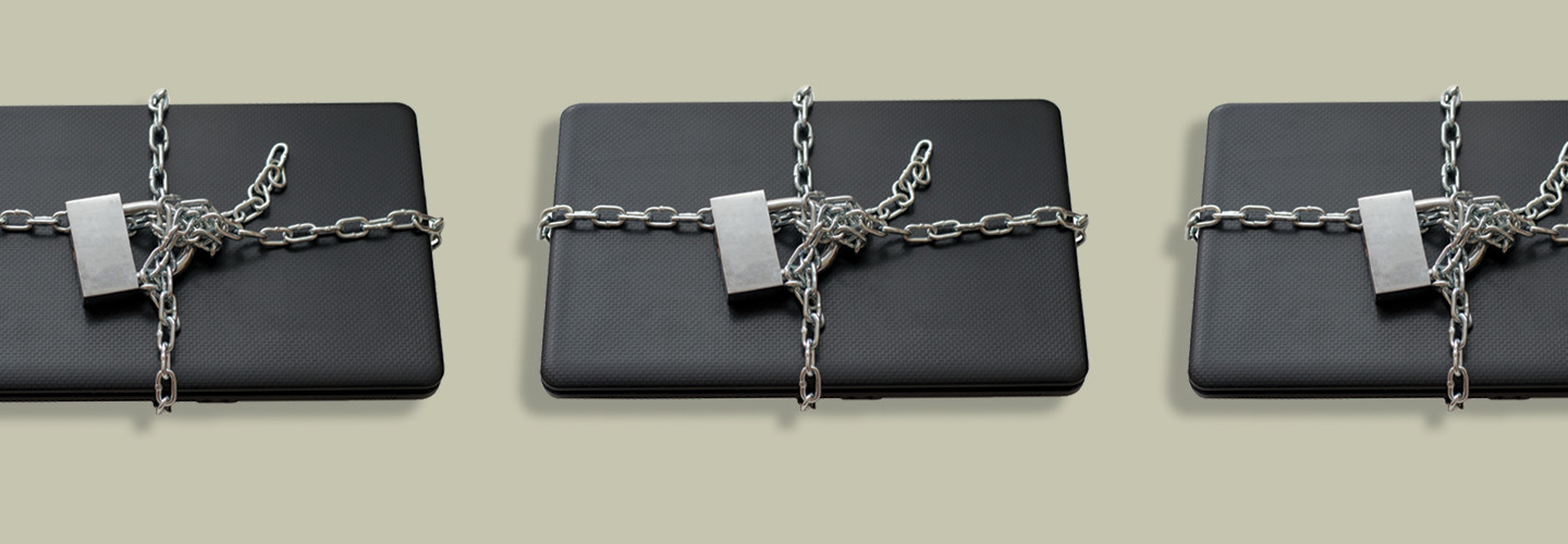 Closed laptop wrapped around with metal chain and locked with padlock