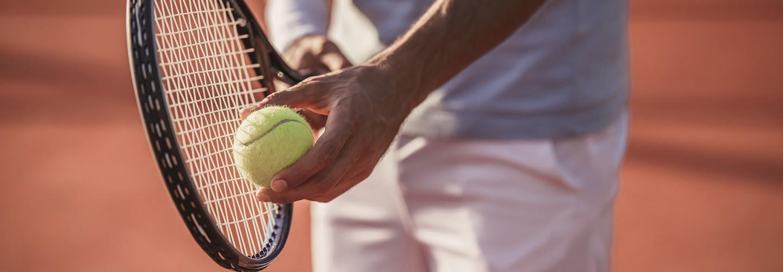 Man about to serve a tennis ball