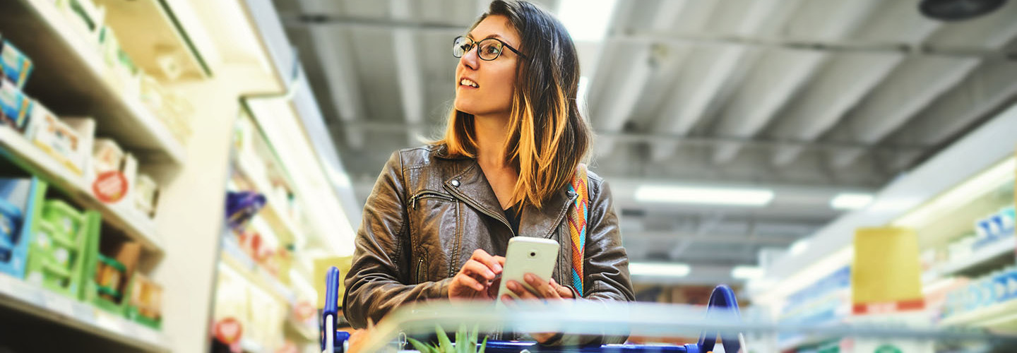 Shot of a young woman using a mobile phone in a grocery store