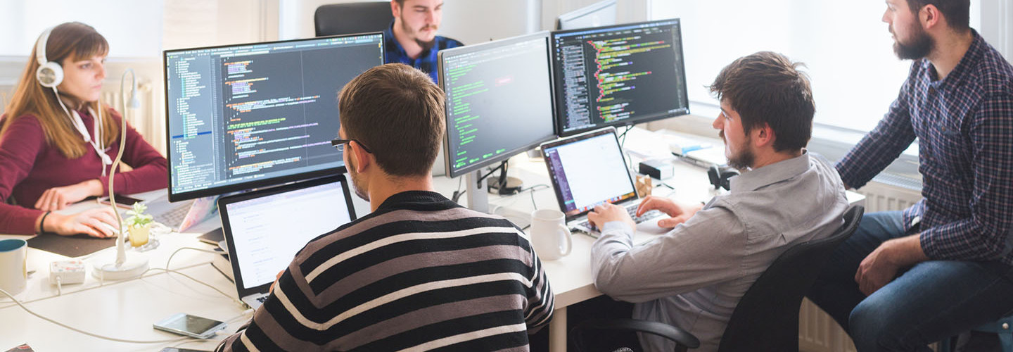 Group of software developers sitting at desktop computers being focused on their work