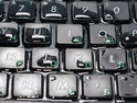 keyboard filled with water on a blue background separately, closeup of a button.