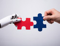 Robot and human hands putting puzzle pieces together
