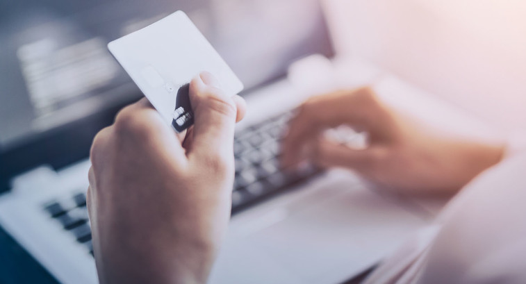 person holding credit card over computer