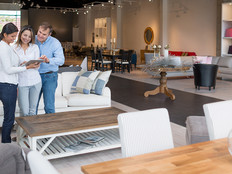 Couple shopping in a retail furniture store being helped by an associate with a tablet