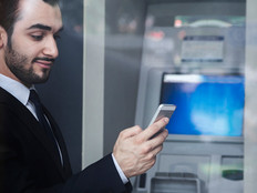 Man using smartphone by bank ATM