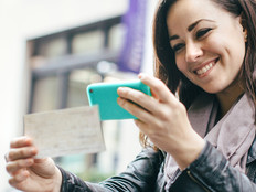 Young woman scanning a check with her smartphone camera
