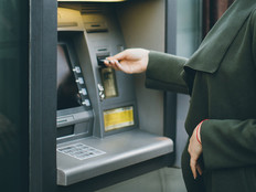 Woman in a green coat using an ATM