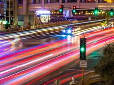 Photo taken above Las Vegas Boulevard (the strip), at night. Many car's light at blurred motion