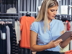 Woman retail worker using a tablet in a clothing store