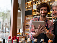 Salesman showing a wine app to a customer on a digital tablet at a winery both looking very happy and smiling