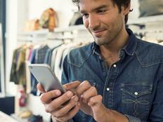 A male shopper standing in a store uses a retail mobile app to learn more information about products that interest him