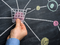Man holding a shopping cart symbol shape over the central node of a multicoloured network drawn on blackboard