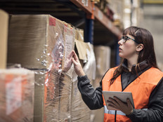 Woman doing inventory of boxes in a warehouse